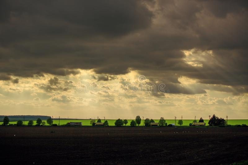 Sunset with dramatic cloudscape over agricultural field and road with cars and trucks.  royalty free stock images