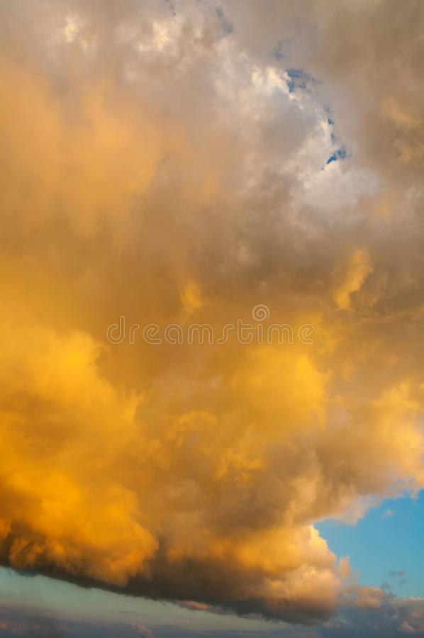Sunset dramatic sky background - pink, orange and blue dramatic colorful clouds lit by evening sunset. Light. Vast sunset sky royalty free stock images