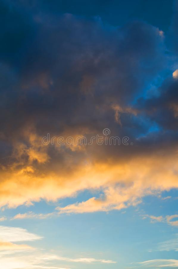 Sunset dramatic sky background - pink, orange and blue dramatic colorful clouds after rain lit by evening sunset light. Vast sunset sky landscape scene stock images