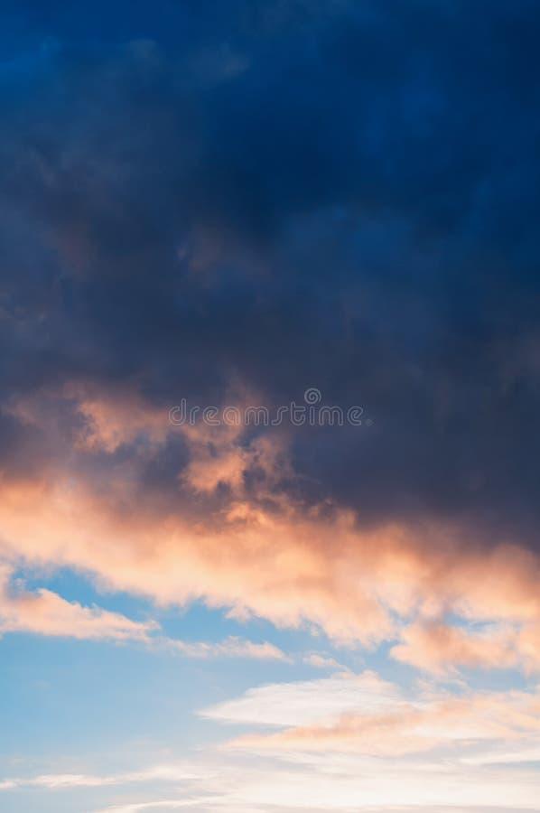 Sunset dramatic sky background - pink, orange and blue dramatic colorful clouds after rain lit by evening sunshine. Vast sunset sky landscape scene stock photos