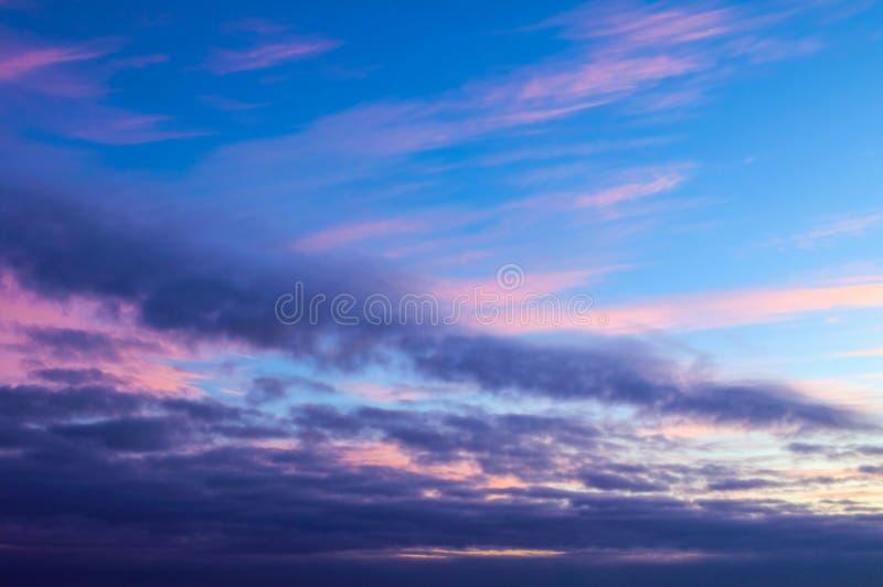 Sunset dramatic sky background - pink, orange and blue dramatic colorful clouds lit by evening sunset light. Vast sunset sky landscape scene stock photos