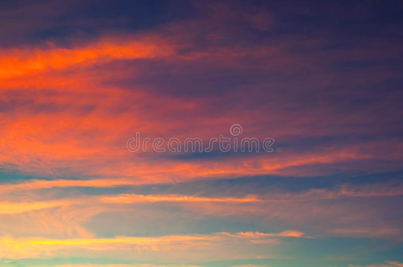 Sunset dramatic sky - red, orange and blue dramatic colorful clouds lit by evening sunset light. Vast sunset sky landscape scene royalty free stock image
