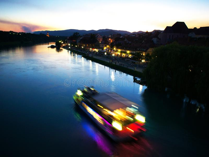 Sunset On Drava River, Maribor, Slovenia. Sunset on Drava river in Maribor, Slovenia during Festival Lent with ship passing by royalty free stock images