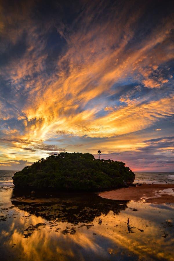 Sunset at Drini beach and the island. Sky, landscape, sunrise, cloud, water, reflection, tourism, vacation, ocean, sea, reef, coast, laguna stock photo
