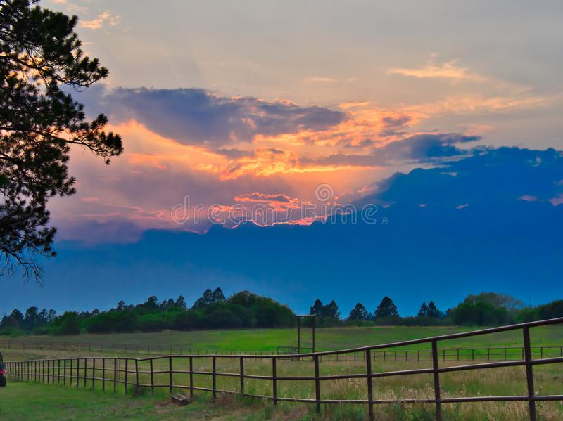 Sunset at Echo Basin Ranch. Wildfire sunset near Mancos, Colorado with green pasture and fence. Echo Basin Ranch stock image