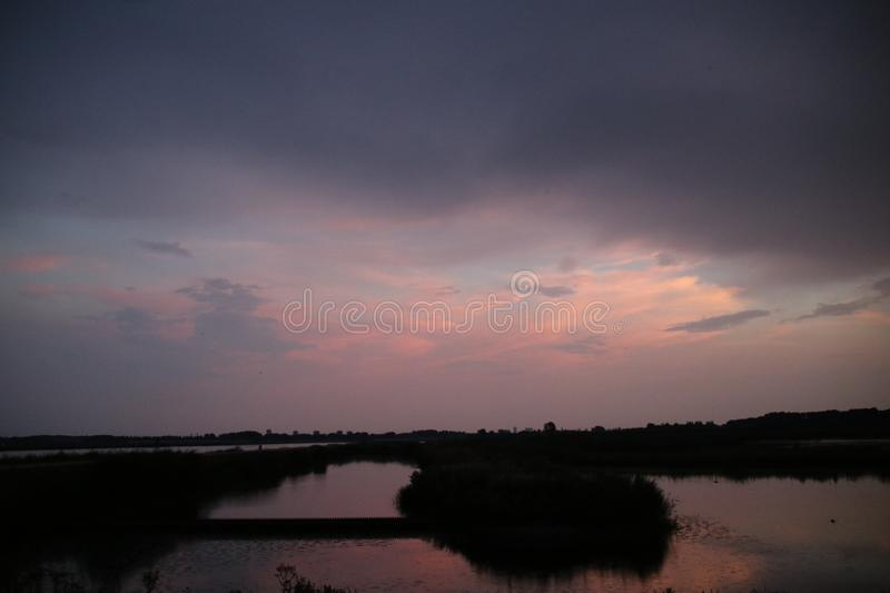 Sunset in the Eendragtspolder in Zevenhuizen, used for water storage from river Rotte to protect Rotterdam against flooding.. Sunset in the Eendragtspolder in royalty free stock photo