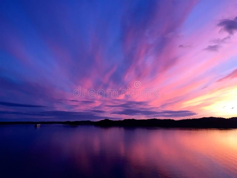 Sunset and ferry seen from Prince Rupert, British Columbia, Canada. On a summer evening near solstice, the view of the water from the town of Prince Rupert royalty free stock photo