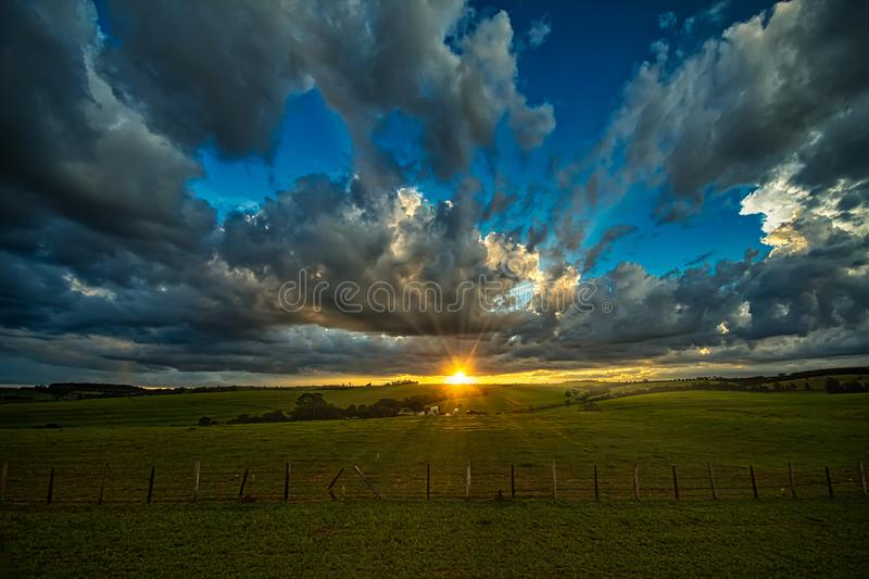 Sunset in field with fence, green pasture and cattle under blue sky with clouds and penetrating sunbeams royalty free stock photo