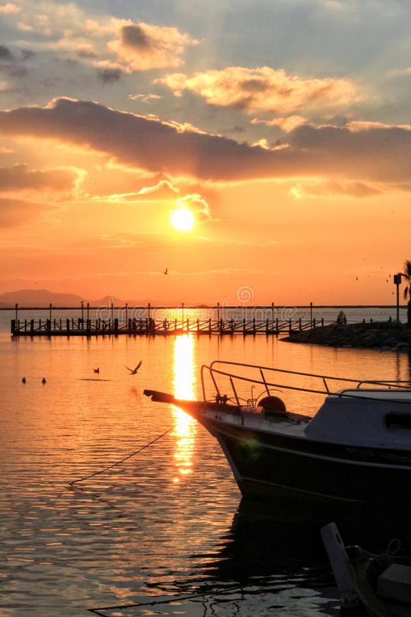 Sunset and fishing boat. Sunset fishing boat sea seagul seagull bird clouds sky nature beauty reflections light summer pier royalty free stock photos