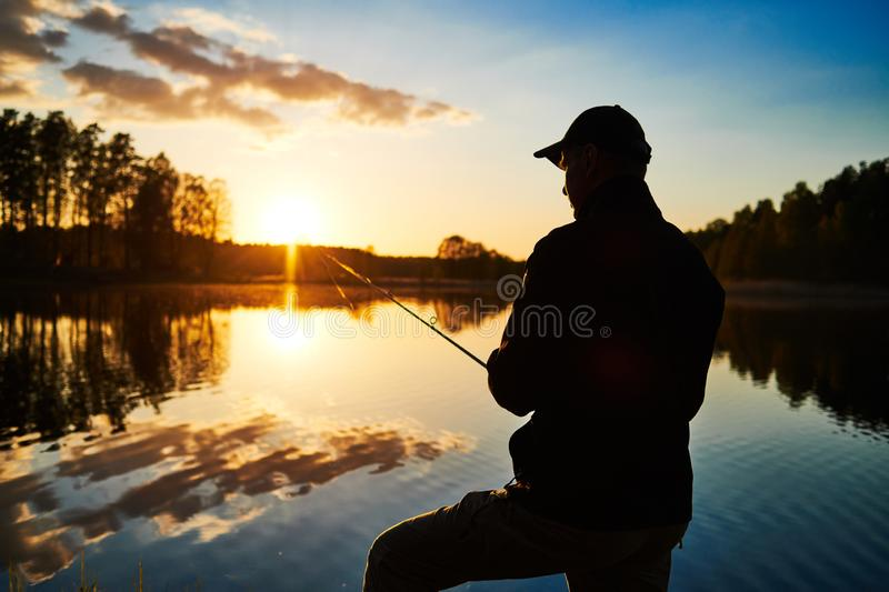 Sunset fishing. fisher with spinning rod royalty free stock image