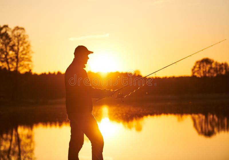 Sunset fishing. fisher with spinning rod royalty free stock images