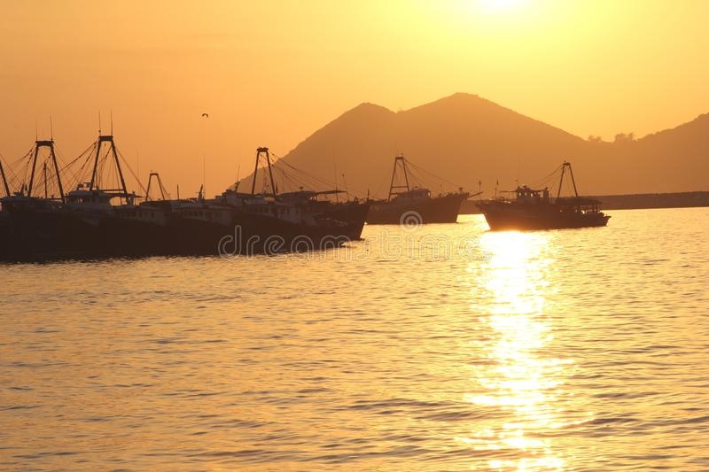 Sunset and fishing vessels, Cheung Chau island, Hong Kong. Fishing vessels in the port of the island Cheung Chau in Hongkong with yellow and orange colors during royalty free stock photography