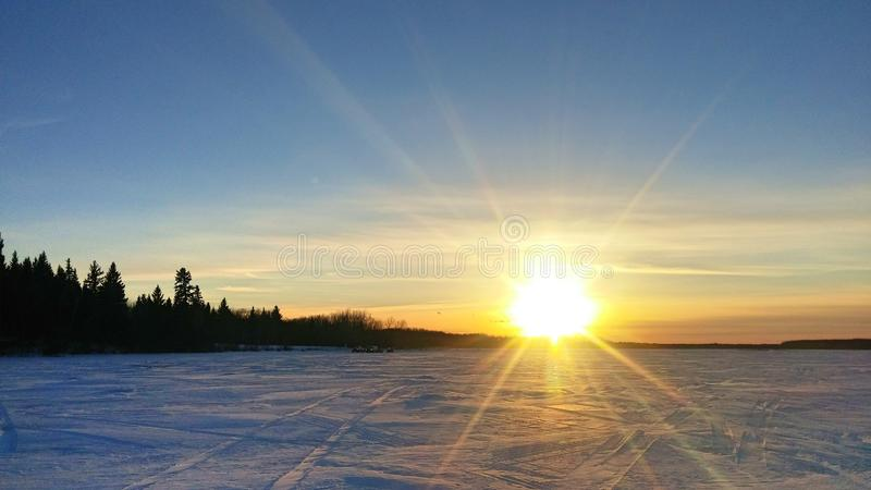 Sunset on a frozen winter lake royalty free stock image