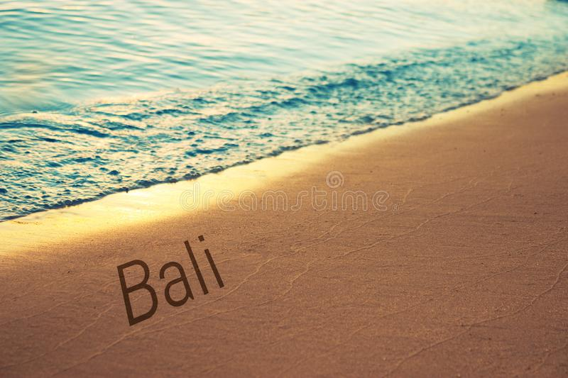 Sunset and Gentle Surf. Bali word written on sand stock photography