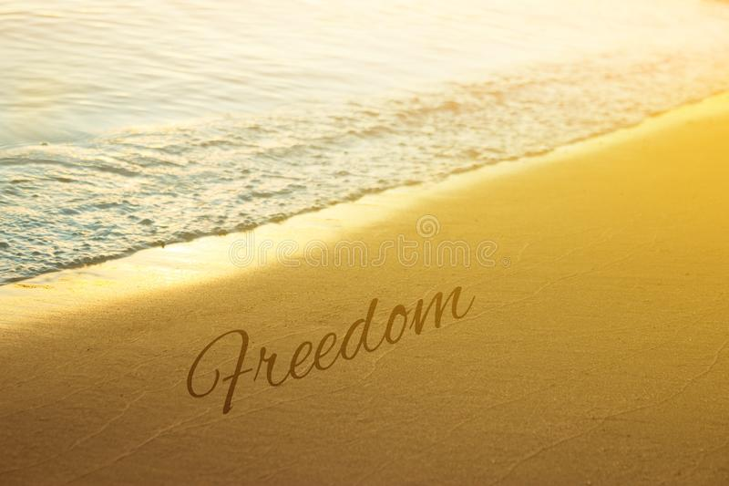 Sunset and Gentle Surf. Freedom word written on sand royalty free stock image