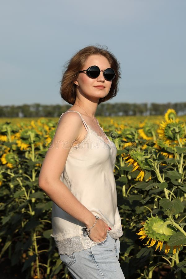 The girl in dark glasses walks on a sunset on the beautiful field of the blossoming sunflowers. royalty free stock photo