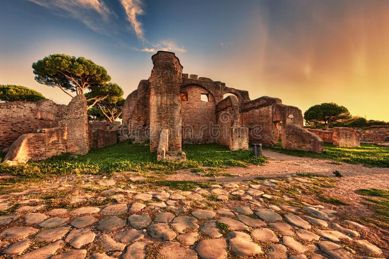 Sunset glimpse from cobblestones street in Ancient Ostia ruins. Rome stock photo