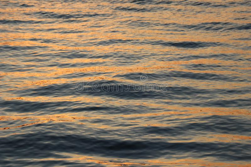 Sunset Glistening Over Ocean Water. The sun sets over the rippling wake of the Atlantic Ocean royalty free stock photography