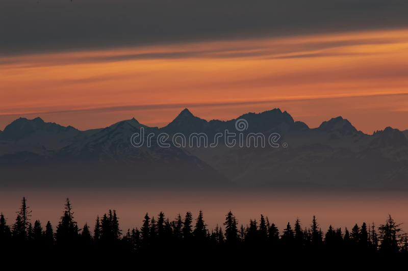 Sunset glow over mountain peaks in a foggy bay. Midnight sunset glow over mountain peaks in foggy Kachemak Bay and Cook Inlet, Alaska royalty free stock photo
