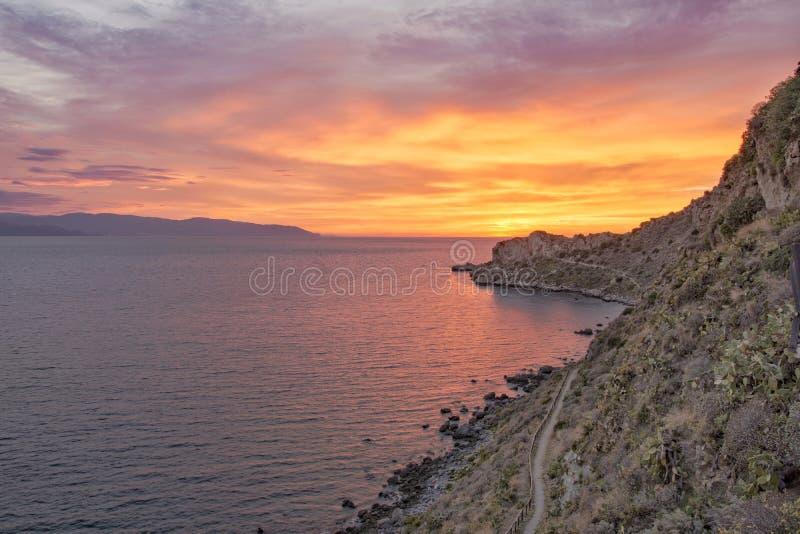 Sunset golden hour rocks in the beach sea horizon stock photography