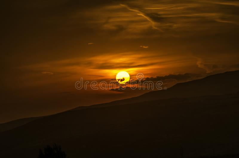 Sunset of the golden solar disk in the sky, late autumn evening over the mountainous terrain of Armenia royalty free stock photo
