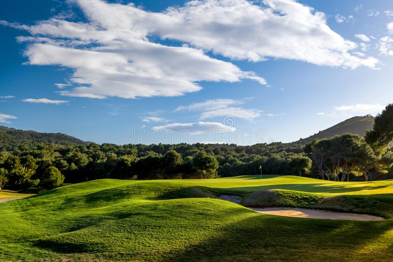 Sunset golf course with trees, blue sky and clouds. A beautiful photo of a golf course with green grass and mountain. Blue sky and clouds. Photo taken in Spain stock image