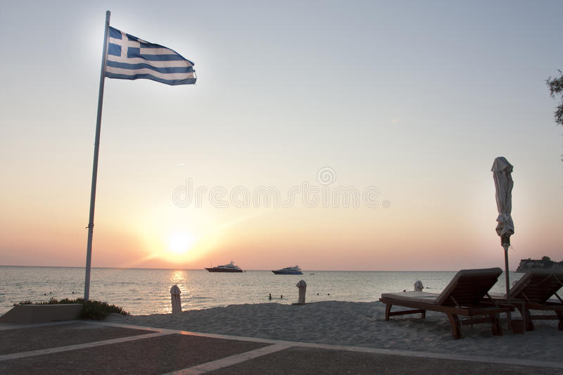 Sunset on a greek beach with yachts in distance