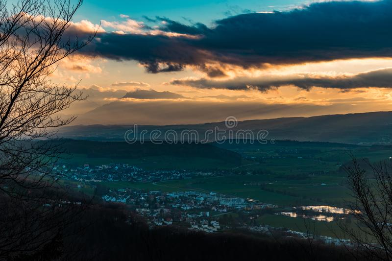 Sunset in the green valley. Sunbeams between sunset clouds fall in the green valley with houses stock image