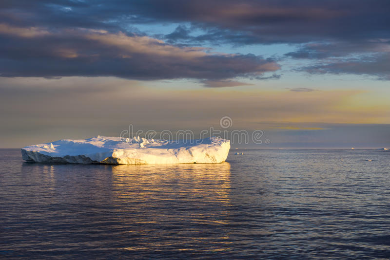Sunset with shiny iceberg, reflecting in Arctic Ocean Iceberg, Greenland royalty free stock photo