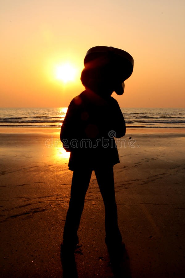Sunset Guitarist. A silhouette of a guitarist looking at the setting sun on a beach royalty free stock photography