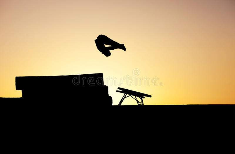 Sunset gymnast. Silhouette of gymnast doing a somersault in pike position stock photography