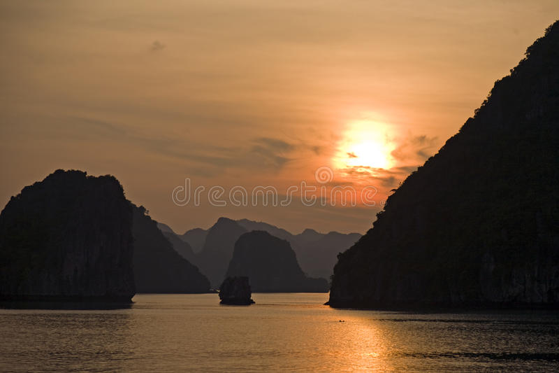 Sunset in Ha Long Bay. The setting sun sets fire to the sky in deep colors of orange and red in vietnam's Ha Long Bay stock photography