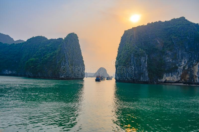 Sunset in Ha Long Bay, Vietnam. Boats, rock formations, misty mood, sunset and reflections in the South China Sea, Vietnam. Halong Bay is a Unesco World Heritage royalty free stock images
