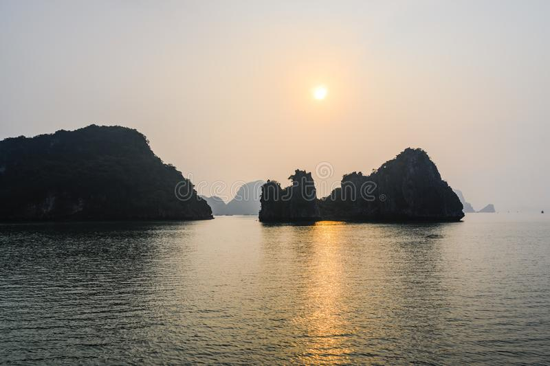 Sunset in Ha Long Bay, Vietnam. Rock formations, misty mood, sunset and refections in the South China Sea, Vietnam royalty free stock photo