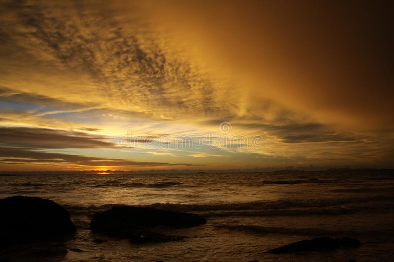 Sunset after heavy rain with arcus shelf storm clouds and stones in the ocean on tropical island Ko Lanta, Thailand royalty free stock photo