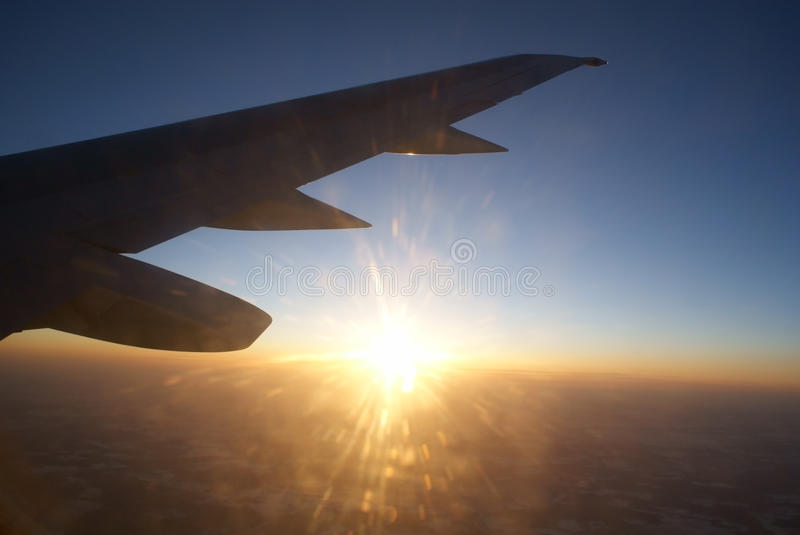 Sunset at the height of the air under the wing stock photo