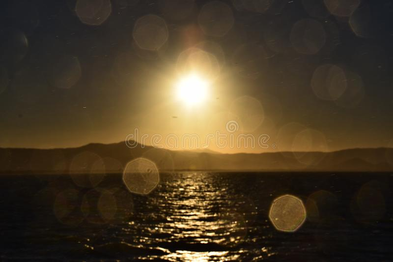 Sunset with a hexagonal blur. Golden yellow sunset just above the mountains, with water droplets creating a hexagonal blur effect royalty free stock image