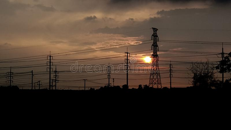 The sunset and High voltage electric pole silhouette stock photography
