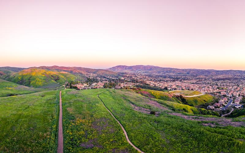 Sunset Hikes and Dirt Trails. A warm sunset over dirt hiking trails in field of mustard. Image captured from an altitude of 90 meters from an aeiral drone stock image