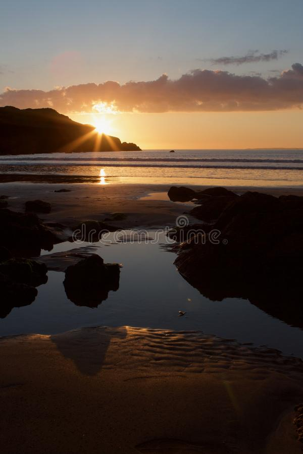 Sunset on Hope Cove beach, Devon, United Kingdom. Still water pool on the beach, a calm sea with sunset behind Bolt Head. Portrait stock image