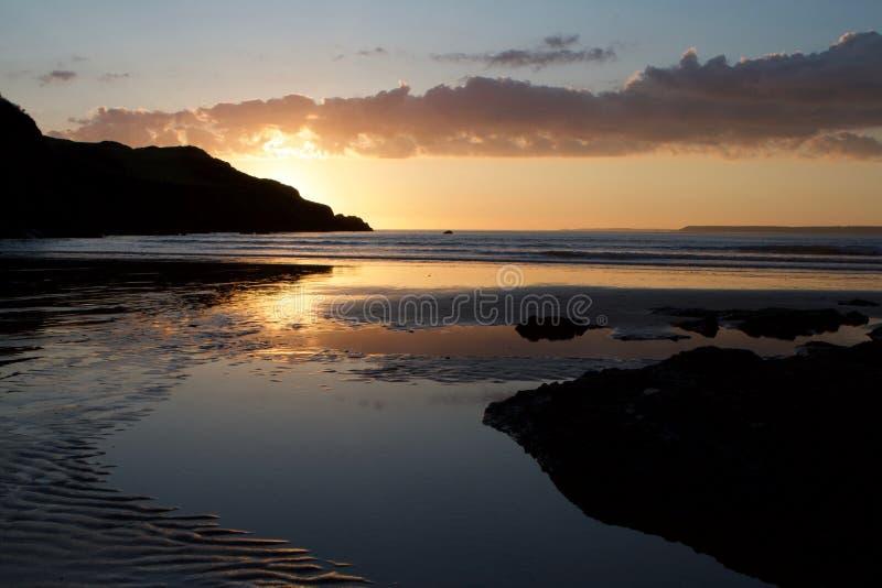 Sunset on Hope Cove beach, Devon, United Kingdom. Still water pool on the beach, a calm sea with sunset behind Bolt Head. Landscape stock photos