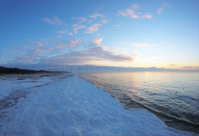 Icy beach. Sunset on the icy beach with snow on the coast of Baltic Sea, Palanga, Lithuania royalty free stock images