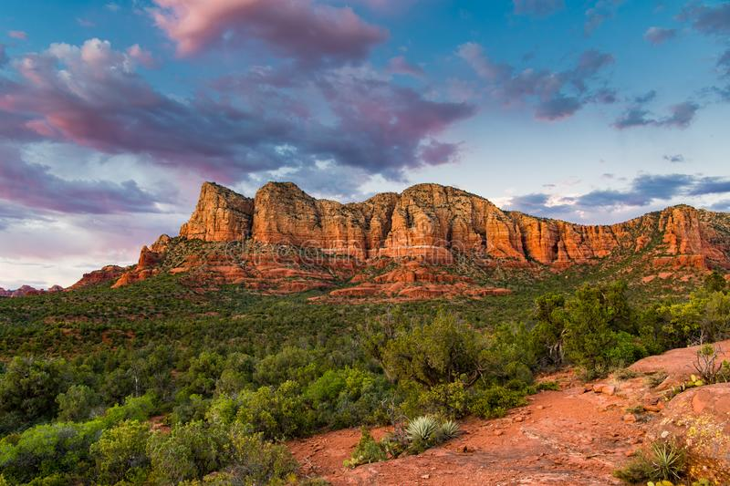 Sunset illuminates a beautiful vast landscape of red rock formations and green juniper tree forest below colorful clouds royalty free stock photo