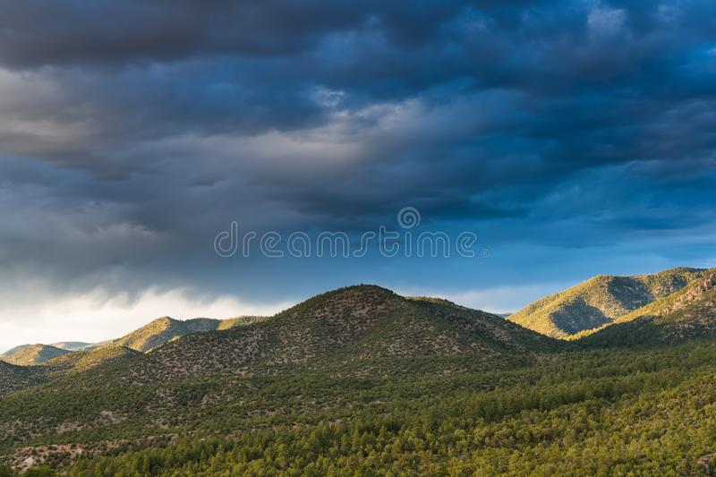 Sunset illuminates the pine forest clad hills under a dramatic sky of dark clouds stock images