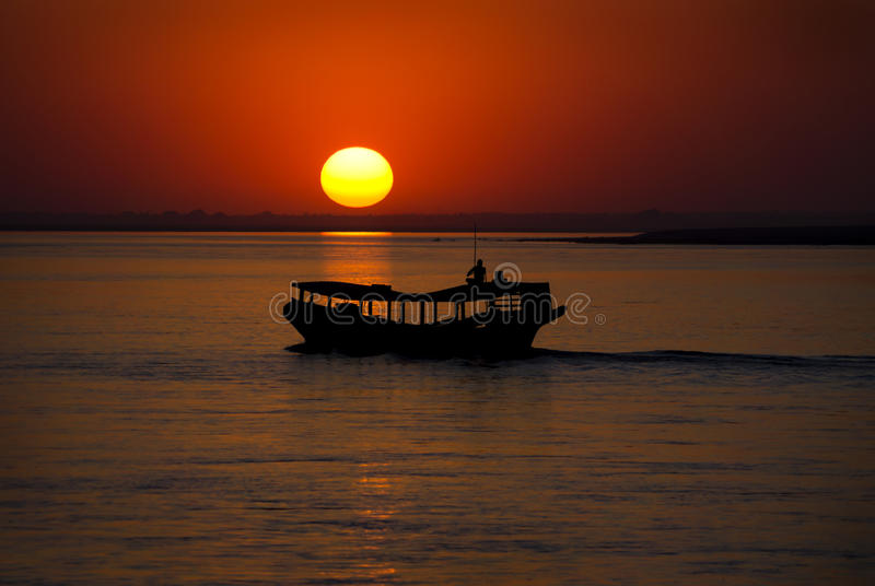 Sunset at Irrawaddy river. Scenic sillhouette of a boat during sunset at Irrawaddy river, Myanmar royalty free stock images