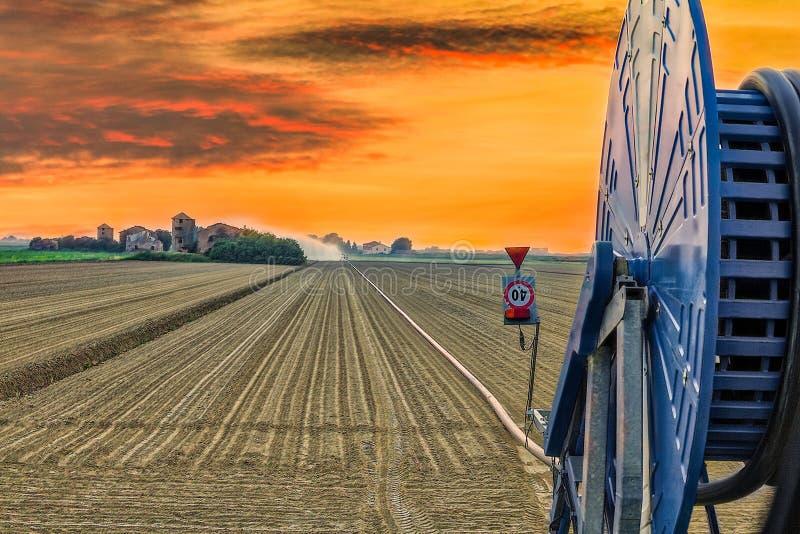 Sunset on irrigating hose. Sunset on hose irrigating fields in Italian countryside stock photo