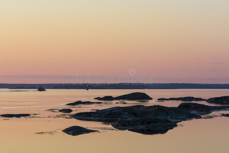 Sunset and islets Landsort Stockholm archipelago. Sunset and islets at Landsort in Stockholm archipelago. A pilotboat approaching lighthouse Grisblänkan on stock image