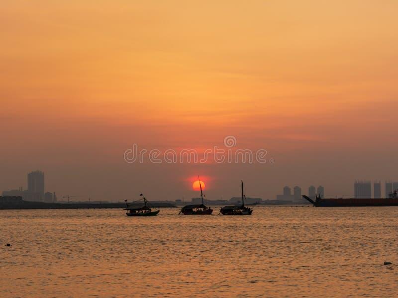 beautiful sunset in jakarta with three boat on ocean stock photo