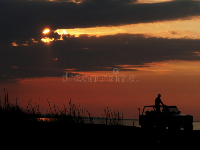 Sunset jeep driving. Silhouette of driving jeep on the beach isolated on the sunset sky. There is one man standing on the vehicle. Sea shore is covered with royalty free stock photo