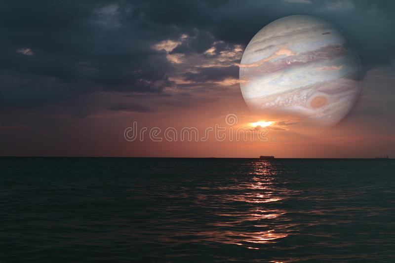 sunset and jupiter on horizontal sea water surface colorful cloud sky stock photo